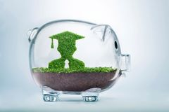 Growing education fund concept. Grass growing in the shape of a graduate student, inside a transparent piggy bank, symbolising the care, dedication and Royalty Free Stock Photos