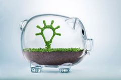 Growing idea investment concept. Grass growing in the shape of a light bulb, inside a transparent piggy bank, symbolising the care, dedication and investment Stock Photos