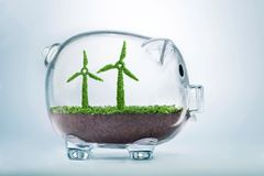 Grass growth wind turbine investment concept. Grass growing in the shape of two wind turbines, inside a transparent piggy bank, symbolising the need to invest in Royalty Free Stock Photos