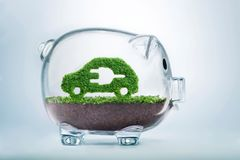 Grass growth electric car investment concept. Grass growing in the shape of a car with a cut out plug, inside a transparent piggy bank, symbolising the need to Stock Photo
