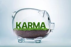 Grass growth karma investment concept. Grass growing in the shape of the word karma, inside a transparent piggy bank Stock Photography