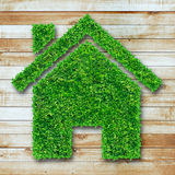 Grass home icon on wooden Stock Photography