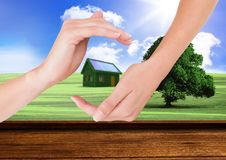 Grass house with panels between hands in the field Royalty Free Stock Photos