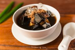 Grass jelly. Dessert herbal gelatin or jelly black with pineapple, syrup, ice, and brown sugar on the wooden background. Chinese style Stock Photo