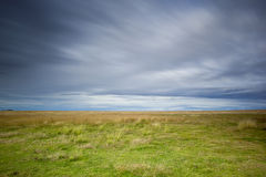 Grass landscape. Grass covered landscape under a cloudy sky Stock Photo
