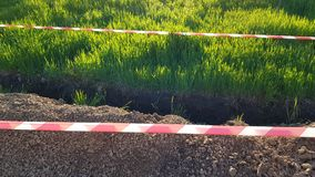 Grass lawn under construction with soil row fenced by red and white safety tape. Park lawn under construction with ground rows fenced by striped safety tape royalty free stock photos