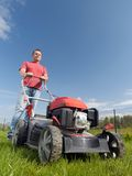 Grass mowing. Man mowing grass with grass-mower Royalty Free Stock Images