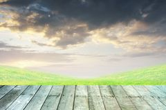 Grass and orange sky with wooden paving. Green grass and orange sky with wooden paving royalty free stock photo