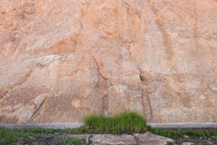 Grass patch rock wall. Grass patch in front of large rock wall stock image