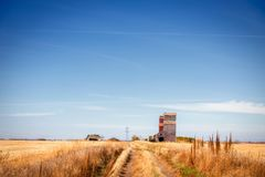 Grass path leading to abandoned grain storage terminal in autumn Stock Image