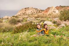On the grass plateau sit two sisters girls in retro clothes are considered sniffing flowers with hills and stormy sea on a backgro. On the grass plateau sit two royalty free stock photography