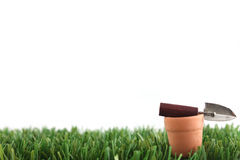 Grass and pot with trowel. Mini clay pot and trowel on grass with copy space stock image
