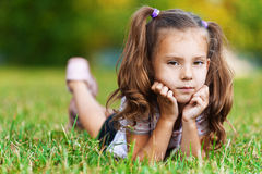 On grass is pretty sad little girl. Against background of green grass (meadows) is sad cute girl (child) with two tails leaning on palm Royalty Free Stock Photo