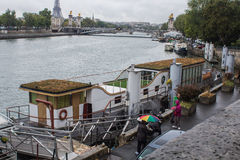 Grass-roofed houseboat moored in sight of Pont Alexandre III on Stock Photo