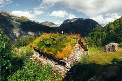The grass-roofed houses in Norway. Typical norwegian old wooden houses with grass roofs near Sunnylvsfjorden fjord and famous Seven Sisters waterfalls, western Royalty Free Stock Photo