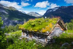 The grass-roofed houses in Norway. Typical norwegian old wooden houses with grass roofs near Sunnylvsfjorden fjord and famous Seven Sisters waterfalls, western Royalty Free Stock Image