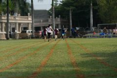 Grass runner track with blur back of athletes stock images