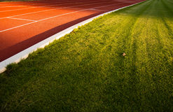 Grass with running track and sunset. Royalty Free Stock Image