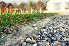 Grass separated from aggregate. Wood piece is separating the aggregate and the grass in a garden Stock Image