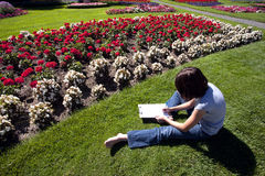 In the grass sketching flowers. A young girl sits on the grass and sketches a flower from a flower garden Royalty Free Stock Image
