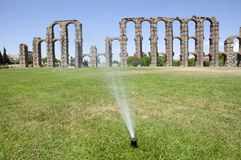 Grass Sprinklers wtih Roman Aqueduct Royalty Free Stock Photos