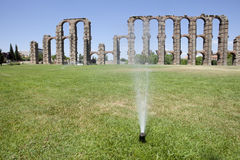 Grass Sprinklers wtih Roman Aqueduct. Of Merida at the bottom. Extremadura, Spain Royalty Free Stock Photography