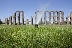 Grass Sprinklers wtih Roman Aqueduct. Of Merida at the bottom. Extremadura, Spain Stock Photography