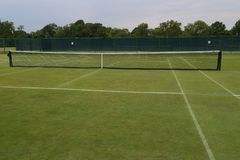 The grass tennis court. In country club stock photo