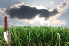 Grass and trowel with storm clouds. Grass and trowel with storm cloud and sunlight royalty free stock photos