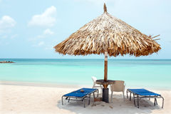 Grass umbrella at the beach on Aruba island Stock Images