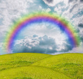 Grass under blue sky. Rainbow over a green glade Royalty Free Stock Image
