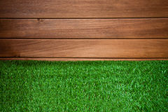 Grass and wood wall, natural background. Synthetic green grass and wooden wall, natural background Stock Images