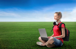 Grassfield. Portrait of a woman with headphones and rucksack sitting on a green meadow and using a laptop Royalty Free Stock Photo