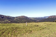 Grassland Against Distand Hills and Blue Sky Landscape Stock Images