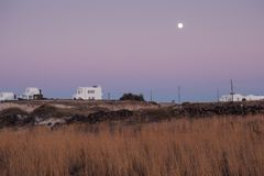Grassland with white houses on horizon. After sundown at full moon Royalty Free Stock Image