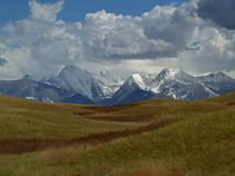 Grasslands and Mountains. This image of the spring grasslands and the rugged snowcapped mountains was taken in western MT Stock Photos