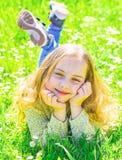 全盛时期概念 笑容的女孩花费休闲户外 孩子享受春天晴朗的天气,当说谎在草甸时 免版税库存照片