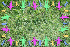 Grassy background with frame made of multicolored paper people Stock Photography