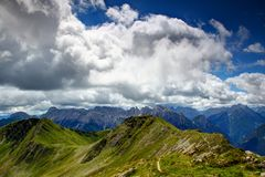 Grassy Carnic Alps main ridge with jagged southern Carnic Alps. Grassy Carnic Alps main ridge with path of Karnischer Hohenweg, in background jagged Rinaldo and Royalty Free Stock Photo