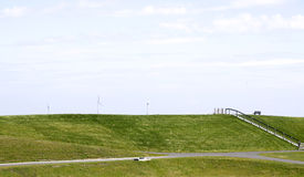 Grassy dike with windturbines Stock Image