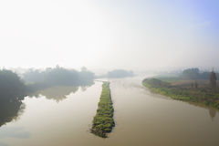 Grassy diversion dike in river of sunny foggy winter morning Stock Images