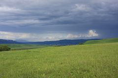 Grassy field and dark clouds Royalty Free Stock Image