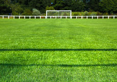 Grassy Field And Goal Post On Sunny Day. Surface level of grassy field with goal post in background on sunny day Royalty Free Stock Photography