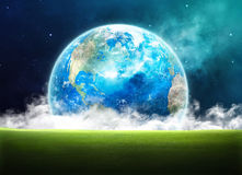 Grassy field in space. Earth rising in space over a green grassy field Royalty Free Stock Image
