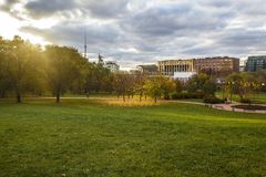Grassy field with trees and a pathway in the distance under a cloudy sky at Rostrkino park in Russia