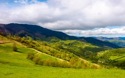 Grassy fields in mountainous rural area. Lovely springtime scenery on a cloudy day Stock Image