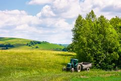 Grassy fields on rolling hills in summer. Beautiful countryside scenery in Carpathian mountains under the blue sky with white fluffy clouds. green tractor near Royalty Free Stock Photography