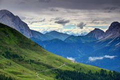 Grassy slopes with dirt road and chalet in Carnic Alps Italy stock photography