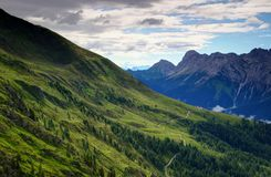 Grassy gentle slopes and rocky peaks of Carnic Alps, Italy Royalty Free Stock Photo