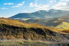 Grassy hill in autumn mountains. Lovely countryside. distant peak in snow on a bright sunny day royalty free stock image